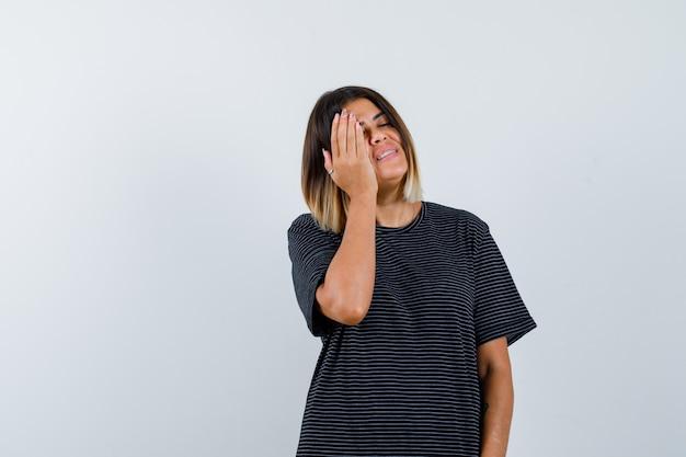 Retrato de uma jovem segurando a mão na bochecha enquanto fecha os olhos em um vestido pólo e está olhando uma linda vista frontal