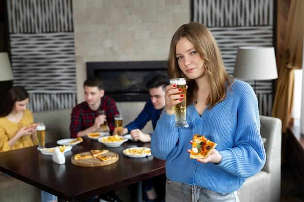 Retrato de uma jovem segurando pizza e cerveja em um bar