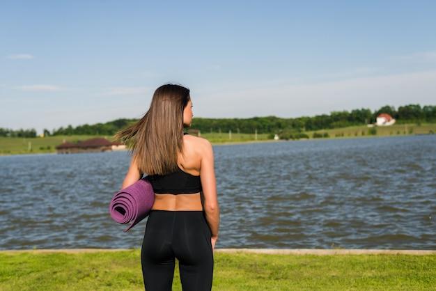 Retrato de uma jovem segurando uma esteira de ginástica ao ar livre no parque