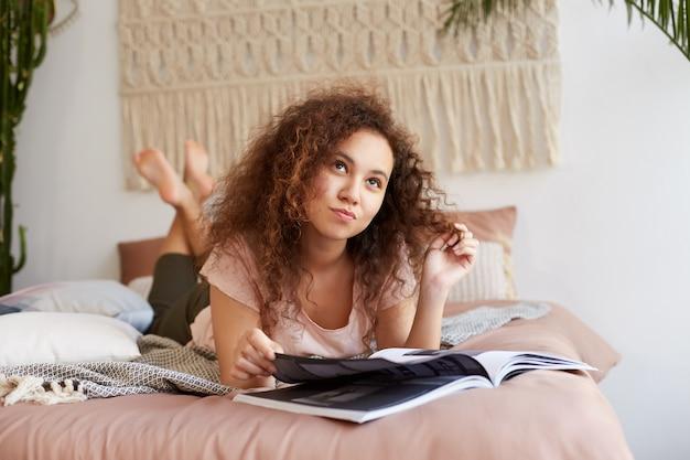 Retrato de uma jovem senhora afro-americana a pensar com cabelos cacheados, deita-se na cama, sonhadoramente desvia o olhar e imagina o vestido que seria como em uma revista e festa de presente.