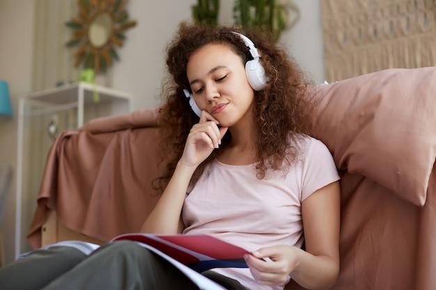 Retrato de uma jovem senhora afro-americana encaracolada de bom pensamento sentado na sala, curtindo sua música favorita e lendo uma nova revista sobre arte, pensativamente desvia o olhar.