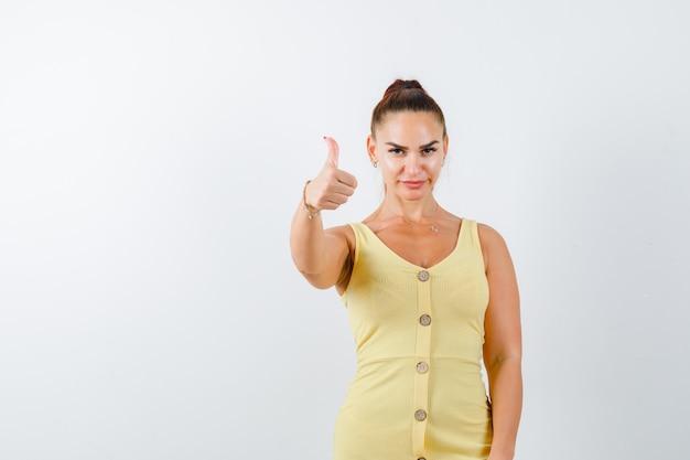 Retrato de uma jovem senhora aparecendo com o polegar em um vestido amarelo e olhando de frente com confiança