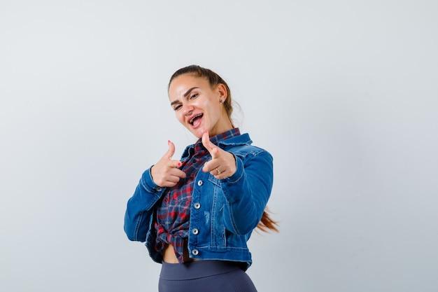 Retrato de uma jovem senhora apontando a pistola de dedo na frente em uma camisa, jaqueta e olhando a vista frontal energética