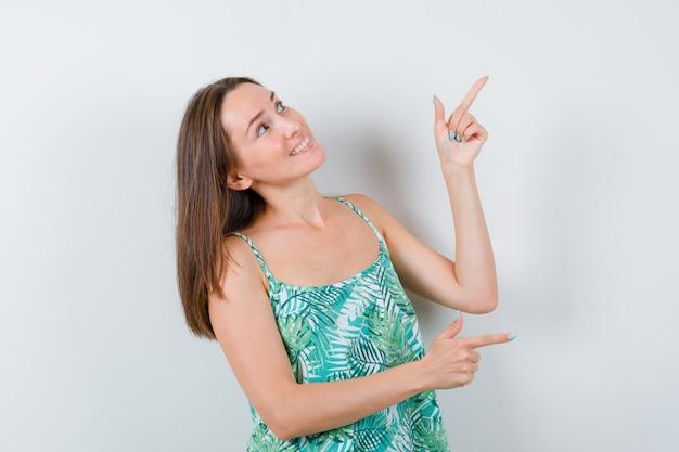 Retrato de uma jovem senhora apontando para o lado direito e o canto direito da blusa e olhando a linda vista frontal