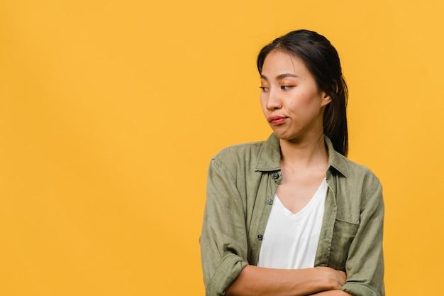 Retrato de uma jovem senhora asiática com expressão negativa, animado, gritando, chorando com raiva emocional em roupas casuais, isolado na parede amarela com espaço de cópia em branco. conceito de expressão facial.