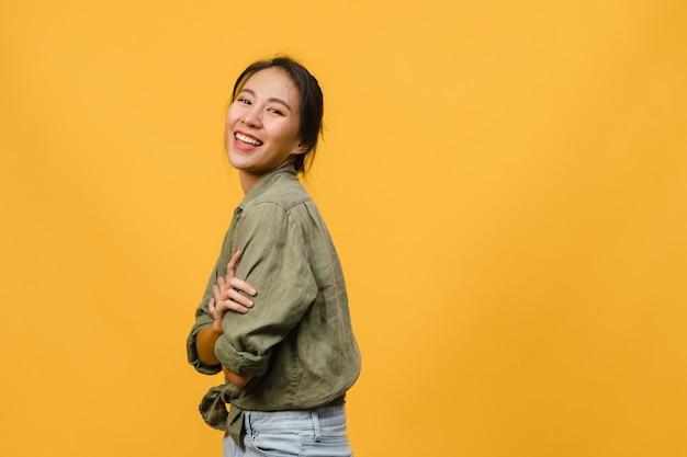 Retrato de uma jovem senhora asiática com expressão positiva, braços cruzados, sorriso largo, vestida com roupas casuais sobre parede amarela. mulher feliz adorável feliz alegra sucesso.