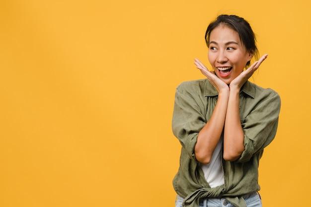 Retrato de uma jovem senhora asiática com expressão positiva, sorriso amplo, vestida com roupas casuais, parede amarela. mulher feliz adorável feliz alegra sucesso. conceito de expressão facial.