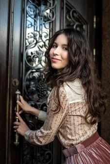 Retrato de uma jovem senhora bonita usando um pano da moda posando perto de portas de textura antigas