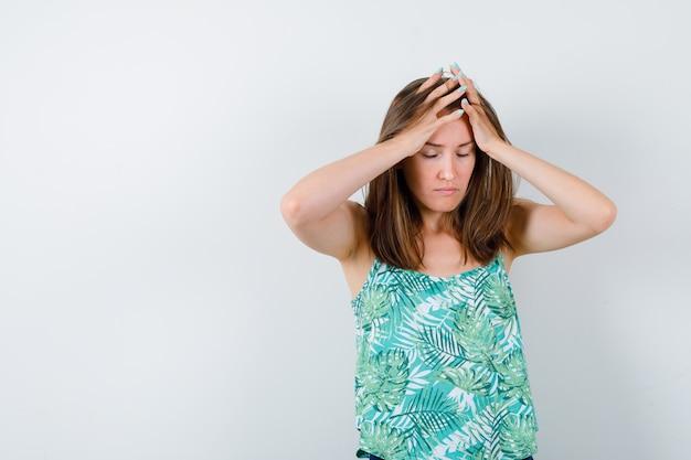 Retrato de uma jovem senhora com as mãos na cabeça dentro da blusa e parecendo exausta.