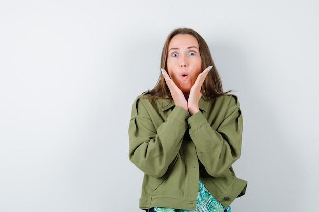 Retrato de uma jovem senhora com as mãos perto do rosto com uma jaqueta verde e olhando para a frente em choque