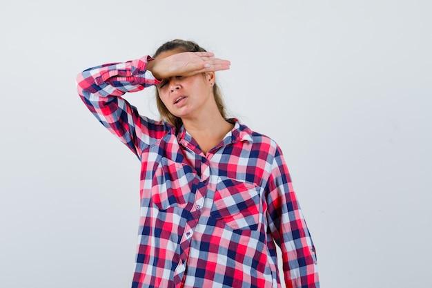 Retrato de uma jovem senhora de mãos dadas em uma camisa quadriculada e olhando irritada de frente