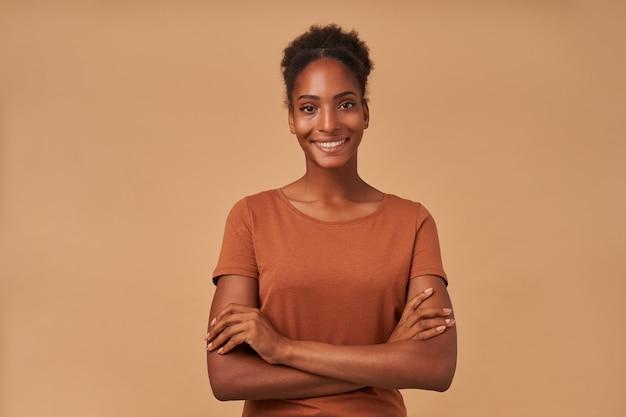 Retrato de uma jovem senhora de pele morena bonita encaracolada com as mãos cruzadas com um sorriso encantador, em pé na cor bege