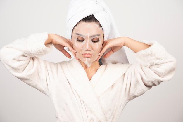 Retrato de uma jovem senhora de roupão e toalha na cabeça enquanto toca seu rosto com a máscara.