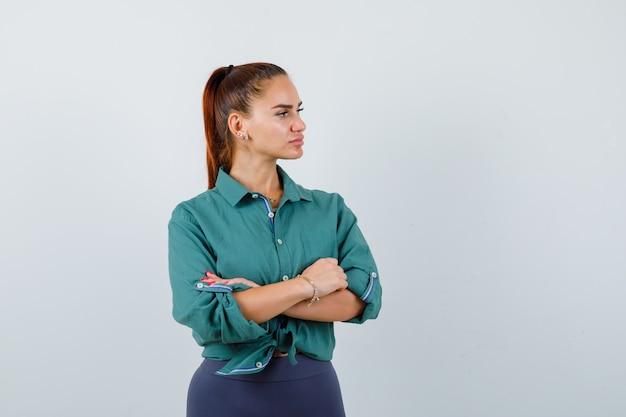Retrato de uma jovem senhora em pé com os braços cruzados, olhando para o outro lado com uma camisa verde e vista frontal pensativa