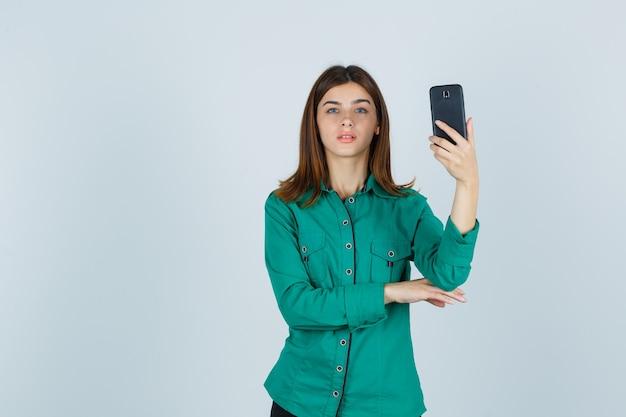 Retrato de uma jovem senhora segurando um telefone celular com uma camisa verde e olhando séria para a frente