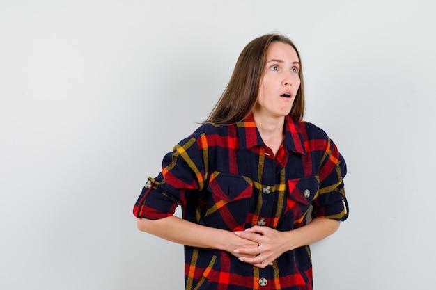 Retrato de uma jovem senhora sofrendo de dores de estômago em uma camisa casual e parecendo indisposta