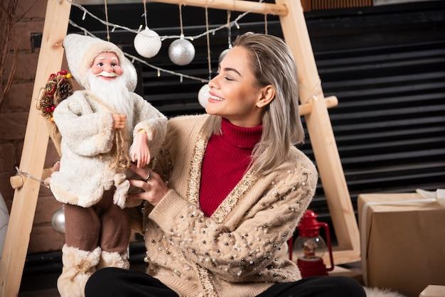Retrato de uma jovem sentada e posando com um brinquedo de papai noel. foto de alta qualidade.