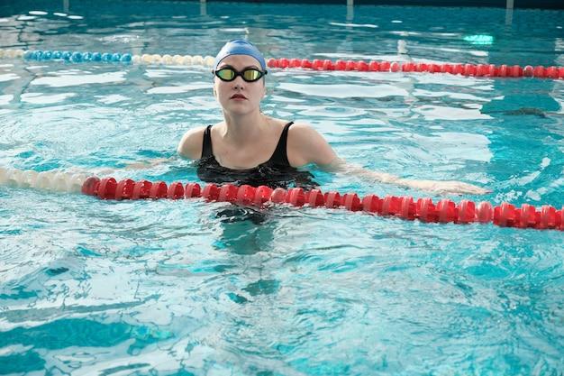 Retrato de uma jovem séria de boné e óculos de proteção, nadando em uma piscina com água limpa