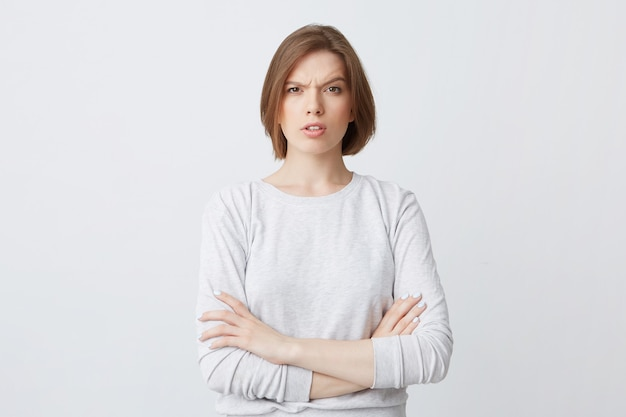Retrato de uma jovem séria e confusa, de manga comprida, de pé com os braços cruzados e parecendo confusa
