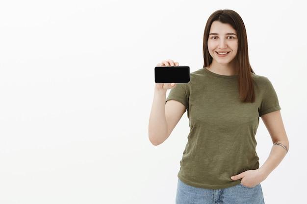 Retrato de uma jovem simpática e feliz feliz morena positiva em uma camiseta casual sorrindo e mostrando o smartphone na posição horizontal como um aplicativo ou telefone celular sobre a parede cinza