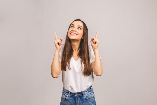 Retrato de uma jovem sorridente apontando o dedo para cima