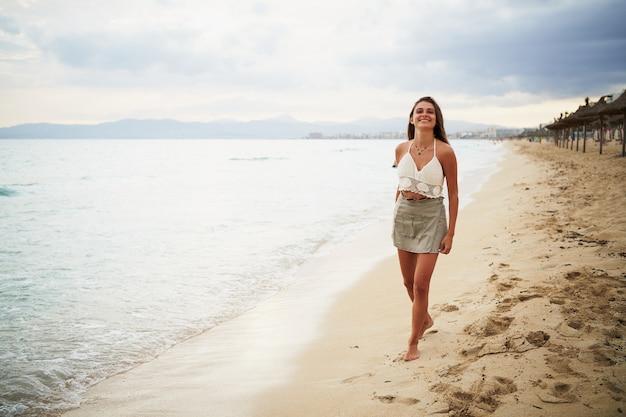 Retrato de uma jovem sorridente caminhando na praia e sorrindo para a câmera