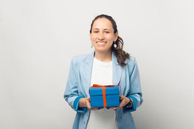 Retrato de uma jovem sorridente casual segurando uma caixa de presente azul sobre fundo branco