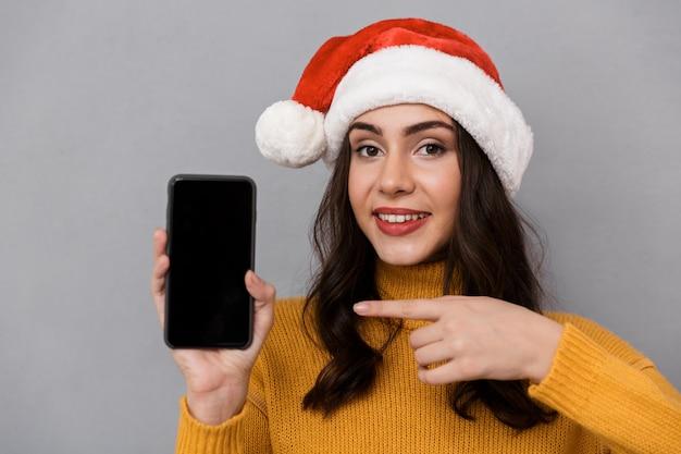 Retrato de uma jovem sorridente com chapéu de papai noel vermelho isolado sobre um fundo cinza, mostrando a tela do celular em branco