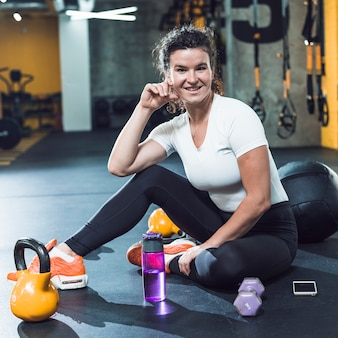 Retrato de uma jovem sorridente com equipamentos de exercício; celular e garrafa de água no chão