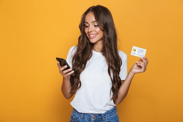 Retrato de uma jovem sorridente com longos cabelos castanhos em pé sobre uma parede amarela, segurando um telefone celular, mostrando um cartão de crédito de plástico