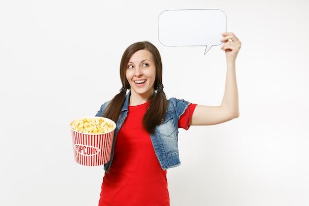 Retrato de uma jovem sorridente com roupas casuais, assistindo a um filme, segurando, digamos, uma nuvem com lugar para texto, copyspace e balde de pipoca isolado no fundo branco. emoções no conceito de cinema