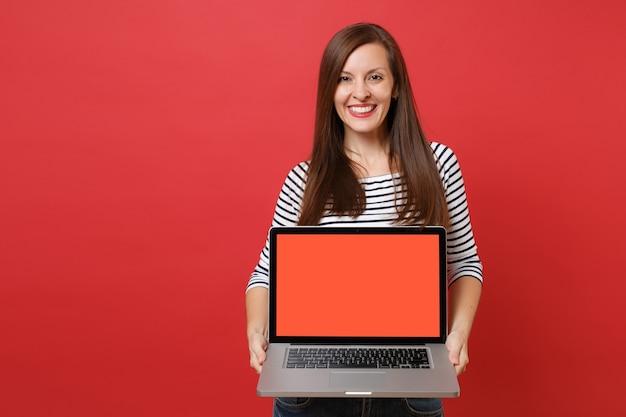 Retrato de uma jovem sorridente com roupas listradas, segurando o computador laptop pc com tela vazia preta em branco, isolada sobre fundo vermelho. emoções sinceras de pessoas, conceito de estilo de vida. simule o espaço da cópia.