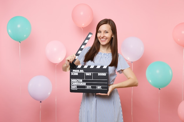 Retrato de uma jovem sorridente com vestido azul, segurando o clássico filme preto, fazendo claquete sobre fundo rosa com balões de ar coloridos. festa de aniversário, conceito de emoções sinceras de pessoas.