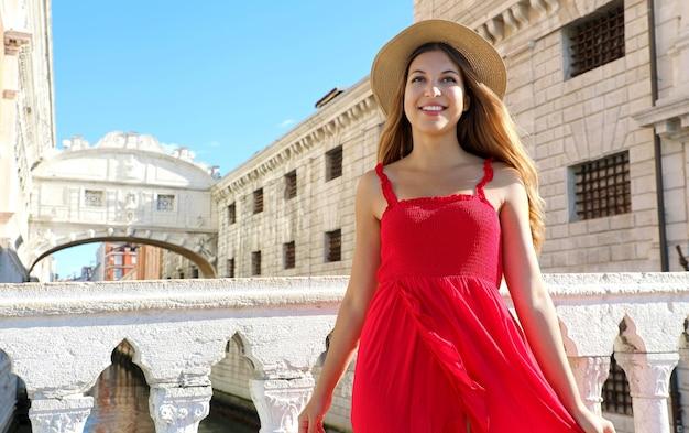 Retrato de uma jovem sorridente com vestido vermelho e chapéu com a ponte dos suspiros de veneza ao fundo, itália