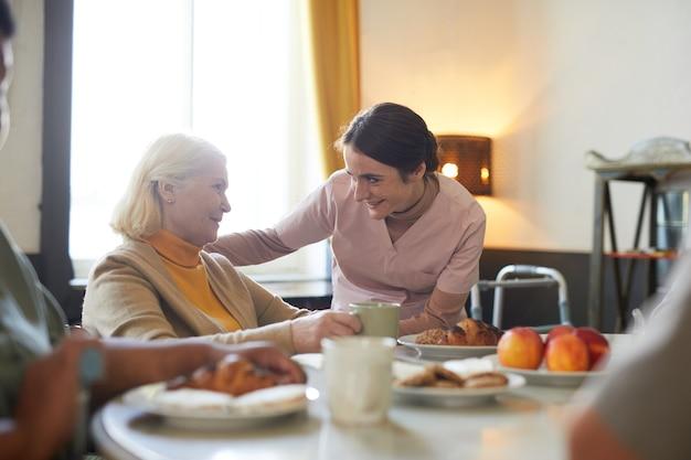 Retrato de uma jovem sorridente cuidando de um paciente sênior no espaço da cópia do lar de idosos