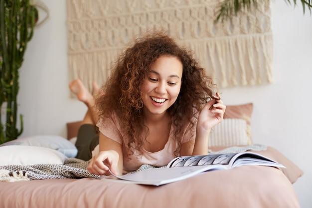 Retrato de uma jovem sorridente de pele escura com cabelo encaracolado, deita-se na cama e lê um artigo de jornal legal na revista, sorri amplamente e aproveita o dia ensolarado de graça.