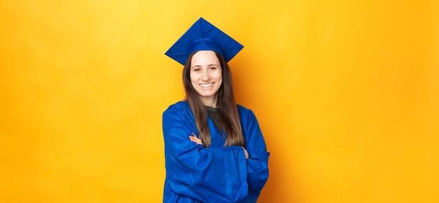 Retrato de uma jovem sorridente e alegre se formando e vestindo uma túnica azul