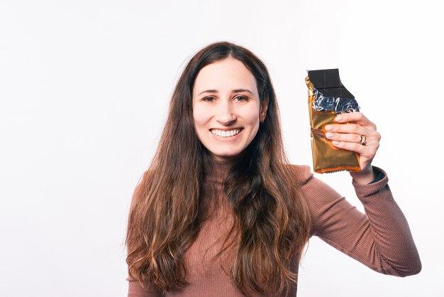 Retrato de uma jovem sorridente e alegre segurando um chocolate amargo sobre fundo branco