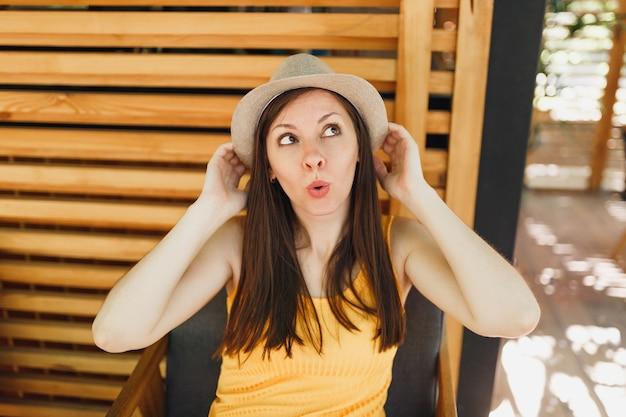 Retrato de uma jovem sorridente e animada com chapéu de palha de verão, camisa amarela coloque as mãos na cabeça na parede de madeira em rua ao ar livre, café, café