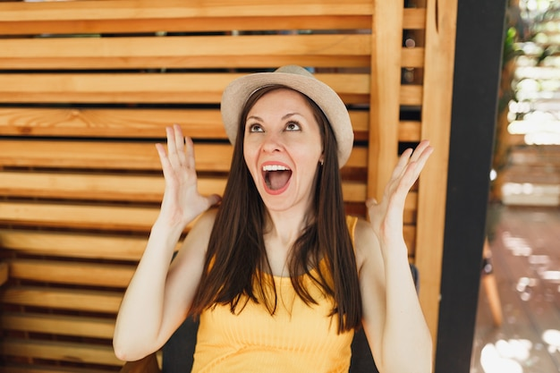 Retrato de uma jovem sorridente e animada com chapéu de palha de verão, camisa amarela, espalhando as mãos na parede de madeira em rua ao ar livre, café, café, verão