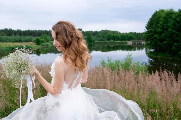 Retrato de uma jovem sorridente e atraente noiva elegante em um vestido de noiva elegante branco com buquê de casamento