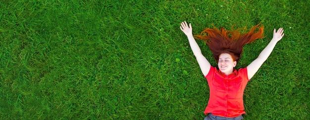Retrato de uma jovem sorridente e ruiva na grama verde do lado de fora do parque