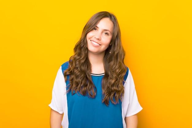 Retrato de uma jovem sorridente em pé sobre um fundo amarelo e olhando para a câmera