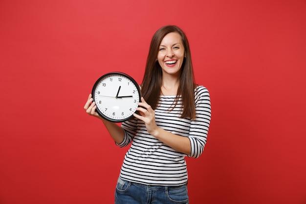 Retrato de uma jovem sorridente em roupas listradas casuais, segurando o relógio redondo isolado no fundo da parede vermelha brilhante. o tempo está se esgotando. conceito de estilo de vida de emoções sinceras de pessoas. simule o espaço da cópia.