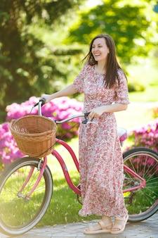 Retrato de uma jovem sorridente em um vestido floral rosa longo, pare de andar em bicicleta vintage com cesta para compras em fundo de flores ao ar livre. tempo de recreação feminino na primavera, parque de verão