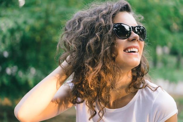 Retrato de uma jovem sorridente feliz em óculos de sol no parque com árvores verdes