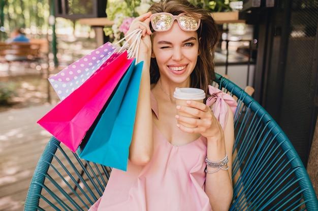 Retrato de uma jovem sorridente feliz mulher bonita com expressão de rosto animado, sentado no café com sacolas de compras bebendo café, roupa da moda para o verão, estilo hippie, vestido rosa de algodão, roupas da moda