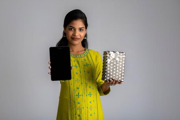 Retrato de uma jovem sorridente feliz segurando a caixa de presente e mostrando o smartphone ou tablet em um cinza.
