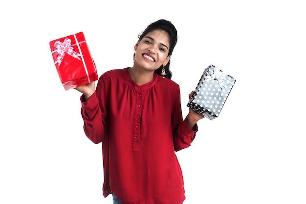 Retrato de uma jovem sorridente feliz segurando e posando com caixas de presente em um fundo branco.