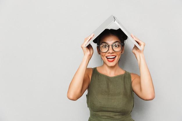 Retrato de uma jovem sorridente isolada, segurando o laptop acima da cabeça